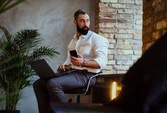 使用一台膝上型计算机的都市有胡子的男性在屋子里 免版税图库摄影