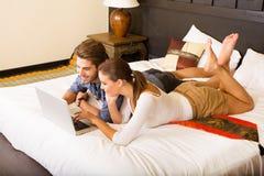 使用一台膝上型计算机的年轻夫妇在一个亚洲旅馆客房 免版税库存照片