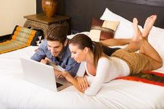 使用一台膝上型计算机的年轻夫妇在一个亚洲旅馆客房 免版税库存图片