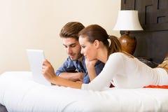 使用一台膝上型计算机的年轻夫妇在一个亚洲旅馆客房 库存图片