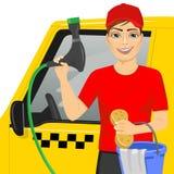 使用一块肥皂的海绵的微笑的青少年的男孩洗涤一辆taxy汽车 免版税库存照片