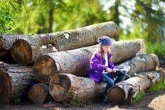 使用一把小折刀的逗人喜爱的小女孩消减森林远足的一根棍子 库存图片