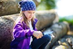 使用一把小折刀的逗人喜爱的小女孩消减森林远足的一根棍子 库存照片