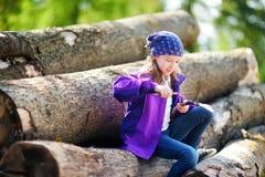 使用一把小折刀的逗人喜爱的小女孩消减森林远足的一根棍子 图库摄影