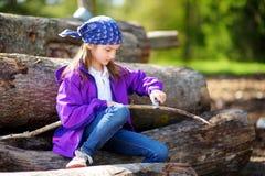 使用一把小折刀的逗人喜爱的小女孩消减森林远足的一根棍子 免版税库存图片