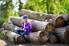 使用一把小折刀的逗人喜爱的小女孩消减森林远足的一根棍子 免版税库存照片