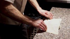 使用一把烹饪铁锹,厨师密封闭合的薄饼并且投入它对烤箱 股票录像