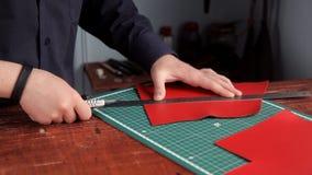 使用一把皮革刀子和统治者,从红色皮革层数人删去了皮肤的准备, 影视素材