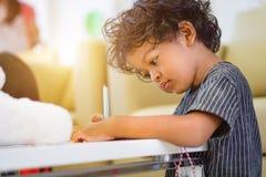 使用一支不可思议的笔的亚裔男孩对写在笔记本和下午光 库存图片