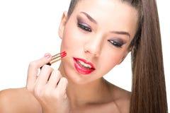 使用一支红色唇膏的美丽的皮肤白皙的妇女 库存照片