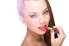 使用一支红色唇膏的美丽的皮肤白皙的妇女 免版税库存图片