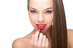 使用一支红色唇膏的美丽的皮肤白皙的妇女 库存图片