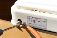 使用一条夹紧的带,安装柔软管对煤气炉 库存图片