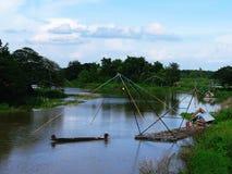 使用一条小船抓鱼在河 免版税库存照片