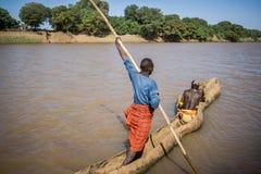 使用一条木小船,人在图尔米,埃塞俄比亚附近横渡奥莫河 免版税库存照片