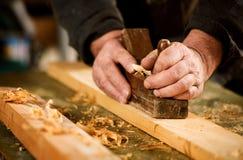 使用一架手扶的飞机的熟练的木匠 库存图片