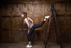 使用一架木梯子的坚强的妇女 库存图片