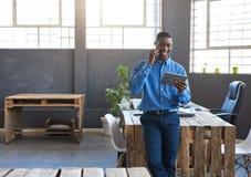 使用一种手机和片剂的微笑的非洲商人在工作 免版税库存照片