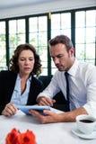使用一种数字式片剂的企业同事,当开会议时 免版税库存图片