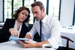 使用一种数字式片剂的企业同事,当开会议时 库存照片