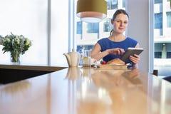 使用一种数字式片剂的妇女在早餐 免版税库存图片