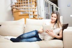使用一种数字式片剂的妇女,当放松时 免版税库存图片