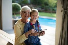 使用一种数字式片剂的孙女和祖母在甲板树荫 免版税库存图片