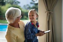 使用一种数字式片剂的孙女和祖母在甲板树荫 库存图片