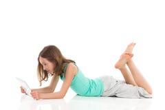 使用一种数字式片剂的小女孩 免版税库存照片