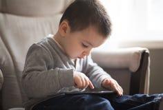使用一种数字式片剂的小男孩坐客厅 库存照片