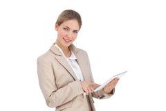 使用一种数字式片剂的微笑的女实业家 免版税库存照片
