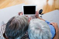 使用一种数字式片剂的资深夫妇在沙发 免版税库存图片