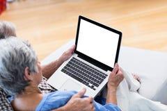 使用一种数字式片剂的资深夫妇在沙发 免版税库存照片
