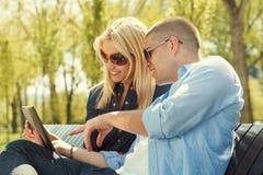 使用一种数字式片剂的年轻夫妇 免版税图库摄影