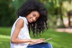 使用一种有触觉的片剂的一个少年黑人女孩的室外画象 免版税库存图片