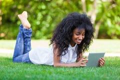 使用一种有触觉的片剂的一个少年黑人女孩的室外画象 库存图片