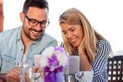 使用一种片剂的微笑的年轻夫妇在咖啡馆 免版税库存图片