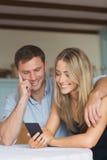 使用一起智能手机的逗人喜爱的夫妇 库存图片