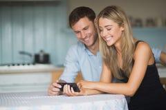 使用一起智能手机的逗人喜爱的夫妇 免版税库存图片