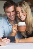 使用一起智能手机的逗人喜爱的夫妇 免版税图库摄影