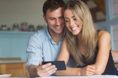 使用一起智能手机的逗人喜爱的夫妇 库存照片
