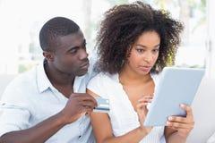 使用一起片剂的有吸引力的夫妇在网上购物的沙发 免版税库存照片
