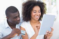 使用一起片剂的有吸引力的夫妇在网上购物的沙发 免版税库存图片