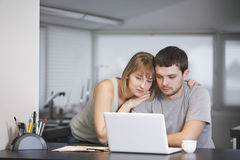 使用一起膝上型计算机的夫妇在厨台 库存图片