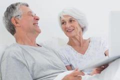 使用一起膝上型计算机的快乐的成熟夫妇 免版税库存照片
