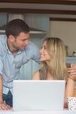 使用一起膝上型计算机的逗人喜爱的夫妇 免版税库存图片