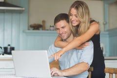 使用一起膝上型计算机的逗人喜爱的夫妇 库存照片
