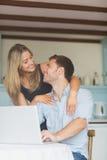 使用一起膝上型计算机的逗人喜爱的夫妇 图库摄影