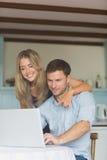 使用一起膝上型计算机的逗人喜爱的夫妇 免版税库存照片