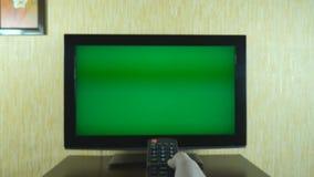 使用一遥控的男性手对翻转在绿色屏幕电视的渠道 人冲浪的电视频道的胳膊与 股票录像